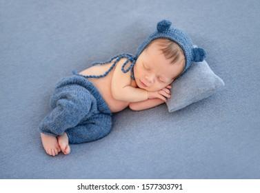 Charming newborn in cute hat sleeping on tiny pillow