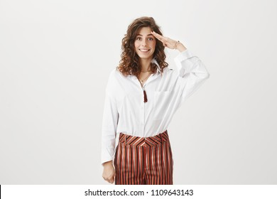 Charming newcomer ready to start working, being energetic and happy, becoming member of company. Portrait of good-looking female in stylish clothes, giving salute with palm over forehead and smiling