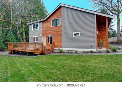 Charming newly renovated home exterior, natural wood and grey siding create a beautiful curb appeal. View of a nice walk out deck with wooden handrails.
