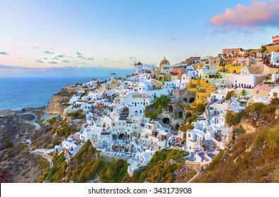 Charming Oia village in last rays of sunset.Panoramic view from a height above the houses, villas and the Mediterranean sea.Beautiful natural landscape.Santorini (Thira) island.Cyclades.Greece.Europe.