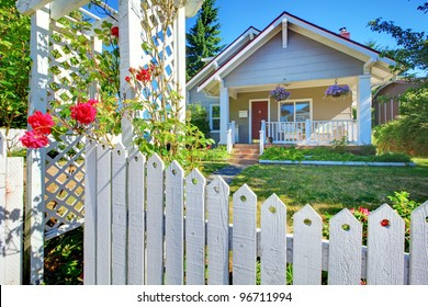Charming old cute grey house behind the white fence with flowers.