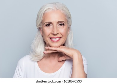 Charming old woman holding hand under chin with beaming smile looking at camera over gray background