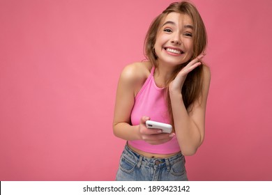 Charming overjoyed young blonde woman wearing pink top poising isolated on pink background with empty space holding in hand and using mobile phone communicating online looking at camera and having fun