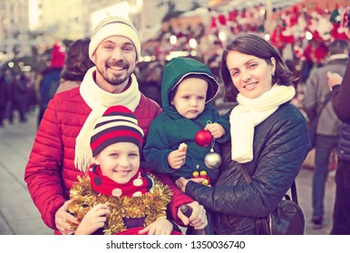 Charming parents with children choosing holidays decorations at Christmas market