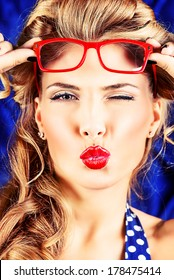 Charming pin-up woman with retro hairstyle and make-up sending a kiss.