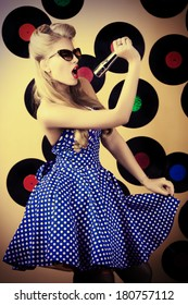 Charming pin-up woman with retro hairstyle and make-up posing with vinyl record.