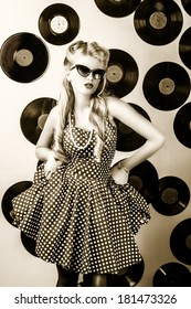 Charming pin-up woman with retro hairstyle and make-up posing with vinyl record. Black-and-white photo.