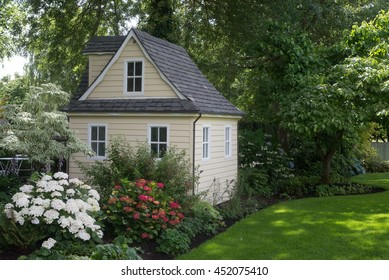 A charming playhouse cottage sits at the edge of a shaded perennial garden.