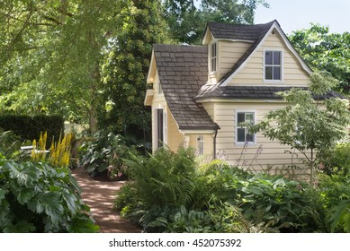 A charming playhouse cottage sits in a shaded perennial garden.