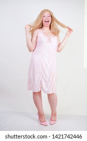 Charming plus size blonde asian girl in pink pretty silk nightgown standing and happy posing on white background in Studio alone. Chubby attractive woman in cute dress.