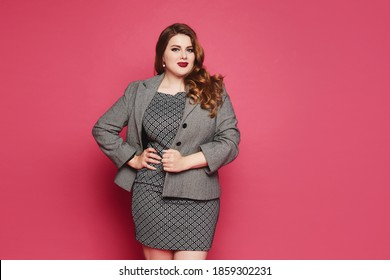Charming plus size businesswoman wearing a grey jacket and dress looking at the camera and standing at pink background, isolated. XXL model in official outfit posing over pink