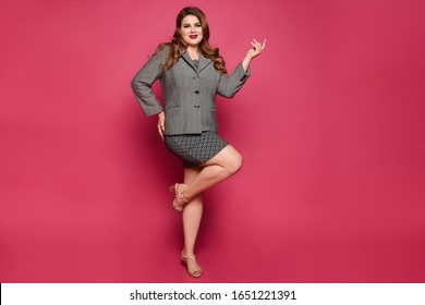 Charming plus size model girl wearing grey jacket and skirt looking at camera and standing on one leg at pink background, isolated. XXL model woman in official outfit posing over pink in full length.