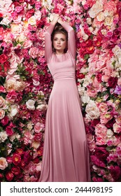 Charming portrait of young beautiful girl in rosy skin-tight gown with dark smoky eyes and natural lipstick, on flowered background made of peony