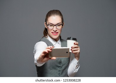 Charming positive office woman with glasses and coffe mug makes selfie on smartphone on gray background