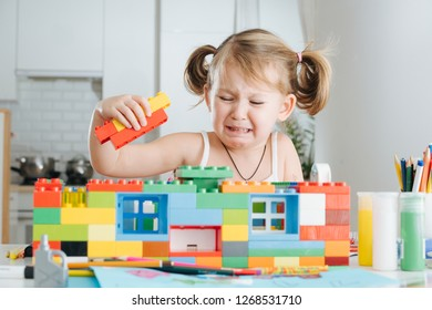 Charming preschooler playing with with two tails doll house constructor at home. Little girl playing with connecting toy cubes. She cries. Can't get it right.