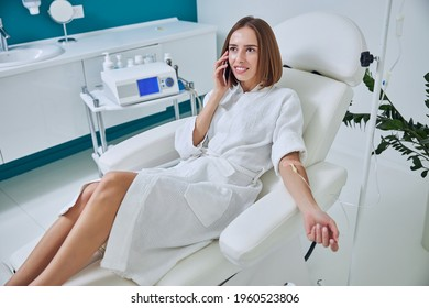 Charming pretty caucasian female sitting in armchair while receiving intravenous vitamin drip treatment in beauty clinic