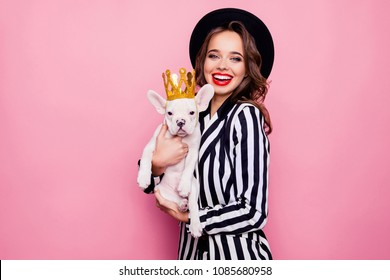 Charming, pretty, cheerful girl with beaming smile, curly hair holding dog on arms, celebrating pet's birthday, animal with gold crown on head, together looking at camera, isolated on pink background