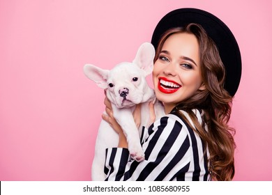 Charming, pretty girl with beaming smile and make up holding dog in hands near face, together looking at camera