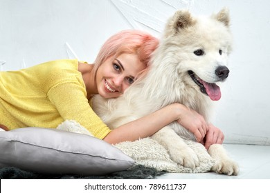 Charming pretty girl looking at camera and hugs her dog, young woman smiles widely and shows beautiful white teeth. A huge white dog looks into distance, his tongue, it hot from the arms of the owner.