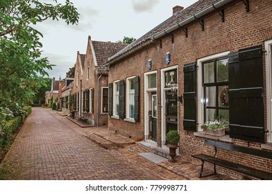 Charming and quiet alley with brick rustic houses and greenery in cloudy day at Drimmelen. A lovely small hamlet with harbor and elegant streets. Southern Netherlands.