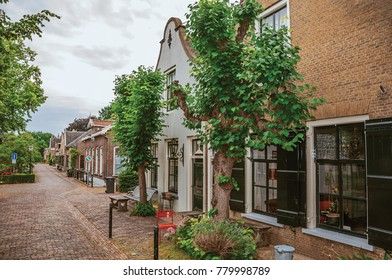 Charming and quiet street with brick rustic houses and greenery in cloudy day at Drimmelen. A lovely small hamlet with harbor and elegant streets. Southern Netherlands.