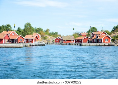 Charming red cottages stand by the seaside at the east coast of Sweden