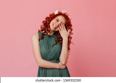 Charming red-haired girl with flowers on her head smiles sweetly and covers her face with her hand. Portrait of lady in green outfit on pink background