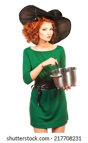 Charming red-haired witch brews a witch's brew. Halloween. Isolated over white.