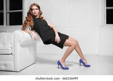 Charming red-haired woman wearing black dress and blue shoes posing near white sofa
