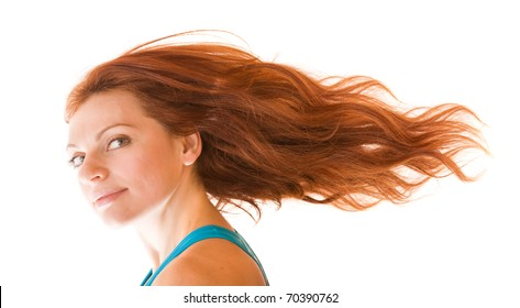 charming red-haired young fit woman with her hair flying away in the wind, isolated on white background