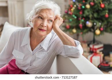 Charming sad old woman is sitting on sofa