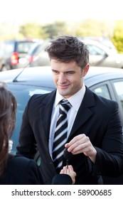 Charming salesman giving a customer car keys outside