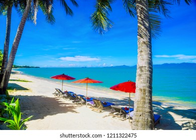 Charming sandy beach, Sunbed with umbrella in tropical calm beach and palm or coconut trees at Maenam Koh Samui Surat Thani Thailand