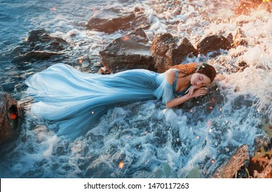 charming sea princess resting on wet stones, girl in blue long tender dress sweetly sleeps in cold water of waterfall with hands under head, sweet red mermaid with kind face in rays of warm sun