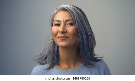 Charming Senior Asian Woman In A Light Sweater Is Posing On The Grey Background.The Lady Is Smiling Gently And Looking Aside .Close-up Shot