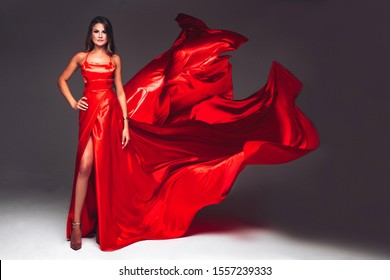 Charming sexy young woman in fluttering red dress. Gray background. Slim body and long hair.