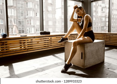 Charming slander girl dressed in black sports top and shorts is sitting on a wooden box in the sunlight in front the window in the gym