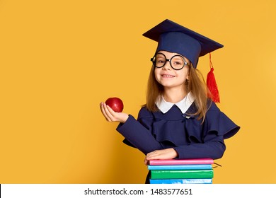 Charming smart girl in glasses and graduation clothes holding red apple while standing at pile of colourful books over yellow background