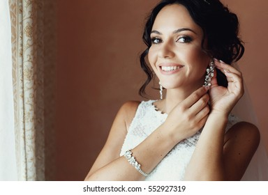 Charming smile of the bride with the beautiful earrings