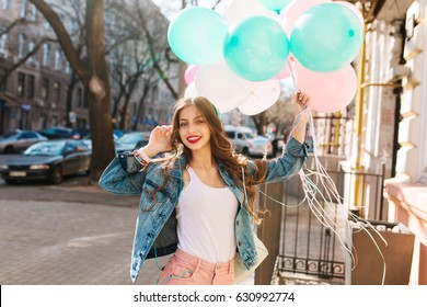Charming smiling girl in denim jacket posing with bunch of colorful balloons on the city background. Portrait of curly young woman with red lipstick going to the friend's birthday party with gift.