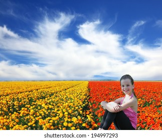 Charming smiling girl with a scythe in a field of blooming yellow and red buttercups