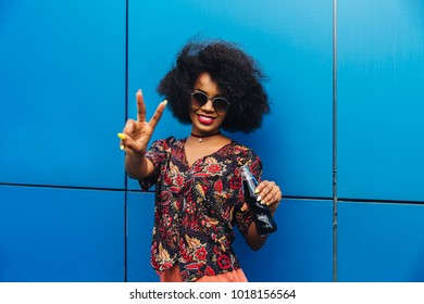 Charming smiling young african woman showing a peace sign at camera, standing with bottle of fresh soda. Dressed in colorful blouse. Outdoors.
