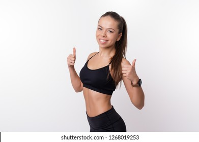 Charming and smiling young fitness woman showing thumbs up over white background