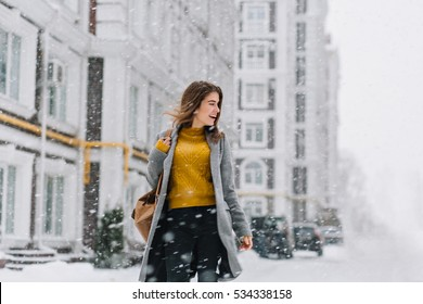 Charming smiling young woman in coat with backpack walking in snowfall in Europe city centre. Expressing positivity, true emotions, enjoy snowing, waiting for christmas holidays, smiling to side