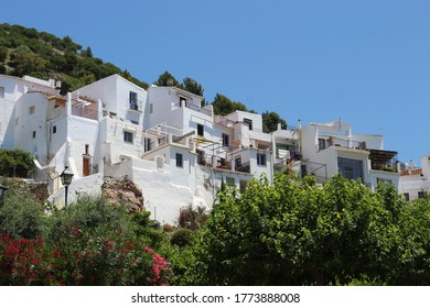 The charming Spanish hill village of Frigiliana, Andalusia  View  of beautiful, traditional town houses on a steep hillside.  Blue sky for copy space