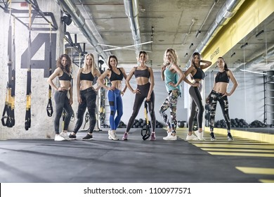 Charming sportive girls are posing in the gym. They are wearing multicolored sportswear: tops, sleeveless, pants and sneakers. Woman are looking into the camera with smiles. Horizontal.