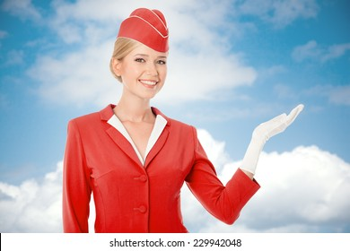 Charming Stewardess Dressed In Red Uniform Holding In Hand. Sky With Clouds Background.