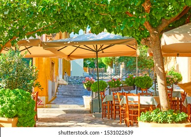 Charming street cafe with tables in a shade of the trees in Plaka district in Athens, Greece