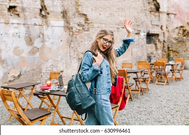 Charming student passed exams perfectly. Adorable girl in a fashionable denim suit leaves the outdoor cafe and says goodbye to friends. Student female, leather bag, jeans jacket, wearing glasses