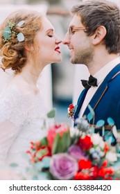 Charming stylish wedding couple softly kissing with eyes closed close up